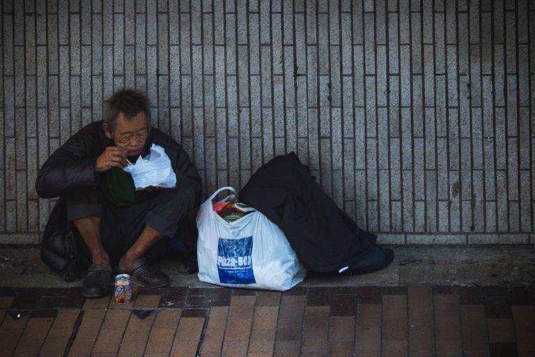 man sitting beside wall